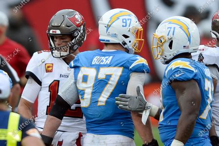 Tampa Bay Buccaneers quarterback Tom Brady (12) shakes hands with Los Angeles Chargers defensive end Joey Bosa (97) and defensive end Damion Square (71) after an NFL football game, in Tampa, Fla