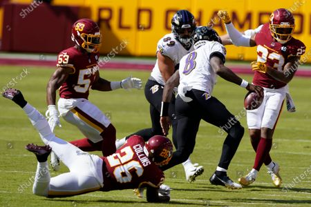 Washington Football Team strong safety Landon Collins (26) trips up Baltimore Ravens quarterback Lamar Jackson (8) during the first half of an NFL football game, in Landover, Md