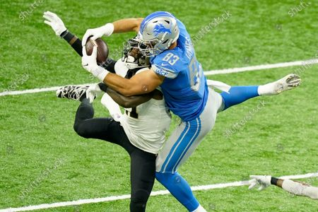 Detroit Lions tight end Jesse James (83), defended by New Orleans Saints strong safety Malcolm Jenkins (27) makes a 31-yard reception during the first half of an NFL football game, in Detroit