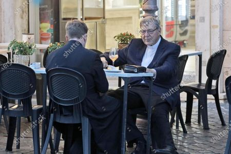 Cardinal George Pell, right, has a drink in a cafe at the Vatican, . Cardinal George Pell, who left the Vatican in 2017 to face child sexual abuse charges in Australia, returned to Rome on Wednesday to find a Holy See mired in the type of corruption scandal he worked to expose and clean up