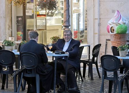Cardinal George Pell has a drink in a cafe at the Vatican, . Cardinal George Pell, who left the Vatican in 2017 to face child sexual abuse charges in Australia, returned to Rome on Wednesday to find a Holy See mired in the type of corruption scandal he worked to expose and clean up