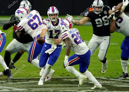 Buffalo Bills quarterback Josh Allen #17 hands off to running back Devin Singletary #26 against the Las Vegas Raiders during the second half of an NFL football game, in Las Vegas