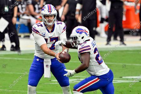 Buffalo Bills quarterback Josh Allen (17) hands off to running back Devin Singletary (26) during an NFL football game against the Las Vegas Raiders, in Las Vegas
