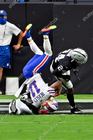 Buffalo Bills wide receiver Cole Beasley (11) catches a pass to score a touchdown over Las Vegas Raiders free safety Lamarcus Joyner (29) and strong safety Johnathan Abram (24) during the first half of an NFL football game, in Las Vegas