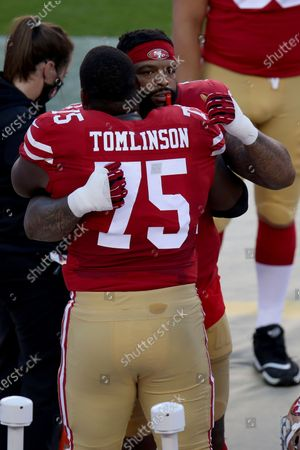 San Francisco 49ers offensive tackle Trent Williams (71) and San Francisco 49ers offensive guard Laken Tomlinson (75) embrace before an NFL football game against the Philadelphia Eagles, in Santa Clara, Calif