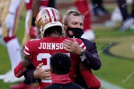 Stock Image of San Francisco 49ers cornerback Dontae Johnson (27) hugs general manager John Lynch before an NFL football game against the Philadelphia Eagles in Santa Clara, Calif