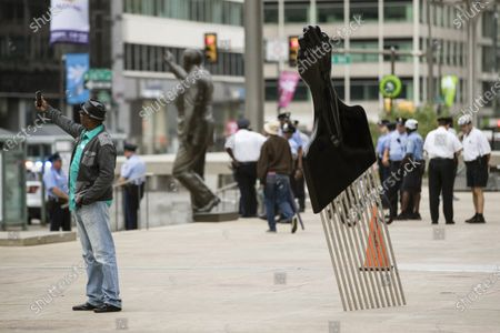 """A man takes a selfie with Hank Willis Thomas' """"All Power to All People"""" sculpture in view of a statue of former Philadelphia Mayor and Police Commissioner Frank Rizzo in Philadelphia. The sculpture was part of an initiative by Monument Lab, a Philadelphia-based group to create public works about issues such as social justice and gentrification. Monument Lab is receiving $4 million from a $250 million project announced Monday by the Andrew W. Mellon Foundation to reimagine the way history is told in public spaces"""
