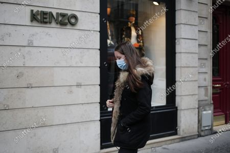 Woman walks oustside a branch of the clothing store Kenzo, founded by the French-Japanese fashion designer Kenzo Takada, in Paris. Takada's family said in a statement to French media Sunday that Takada died from complications from COVID-19 in a hospital in Neuilly-sur-Seine, near Paris. He was 81