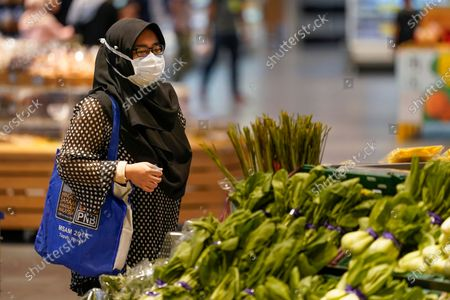 Shopper wearing a face mask to help curb the spread of the coronavirus looks at produce and a grocery in Putrajaya, Malaysia, . Prime Minister Muhyiddin Yassin says he will self-quarantine after a Cabinet minister he was in contact with tested positive for the coronavirus