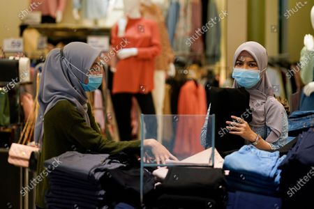 Shoppers wearing a face mask to help curb the spread of the coronavirus shopping at mall in Putrajaya, Malaysia, . Prime Minister Muhyiddin Yassin says he will self-quarantine after a Cabinet minister he was in contact with tested positive for the coronavirus