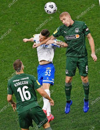 Sebastian Szymanski of Dynamo (center) and Yury Gazinsky of Krasnodar (right)
