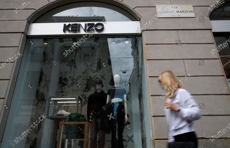 Woman passes by the window of a Kenzo shop in downtown Milan, Italy, . Kenzo Takada, the iconic French-Japanese fashion designer famed for his jungle-infused designs and free-spirited aesthetic that channeled global travel, has died Sunday. He was 81. The family said in a statement to French media Sunday that Takada died from complications from COVID-19 in a hospital in Neuilly-sur-Seine, near Paris. A public relations officer for Kenzo's brand confirmed that Takada died, but didn't give a cause of death