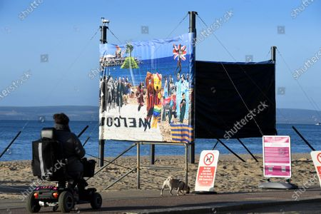 Artwork ban in Bournemouth  One side of the windbreak was deemed acceptable while the other has been covered up by the council.  A satirical artist has hit out at a local council after town hall bureaucrats ordered him to cover up part of his display on a popular beach.  Christopher Spencer, better known as 'Cold War Steve', had hoped to show his double sided windbreak on Boscombe Beach in Dorset.  The 82ft piece was designed to have a 'hopeful side' and a 'dark side' featuring figures from popular culture and politics.  The dark side included a naked Boris Johnson running across the sand and depicted Rupert Murdoch and Nigel Farage as strange monsters.  Dominic Cummings and Vladimir Putin were also included in the chaotic scene.