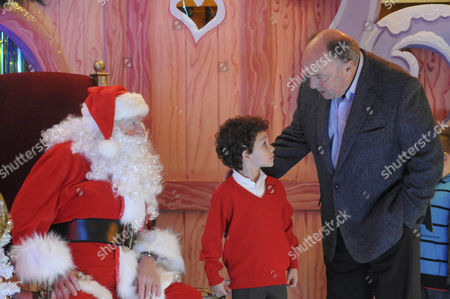 Ken Barlow [William Roache] in the department store playing Santa is horrified when he sees George Wilson [Anthony Valentine] and Simon Barlow [Alex Bain] in the queue.  When it Simon's turn, Ken and George argue and Ken's beard slips which Simon and the other children see.  The manager sacks Ken.