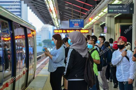 People wearing masks stand in a metro station in Kuala Lumpur, Malaysia, Oct. 5, 2020. Malaysian Prime Minister Muhyiddin Yassin said Monday that he will self quarantine for 14 days after a cabinet minister attending a recent meeting he chaired tested positive of COVID-19.     The announcement came when Malaysia reported another daily record high of 432 new COVID-19 infections on Monday, bringing the national total to 12,813.