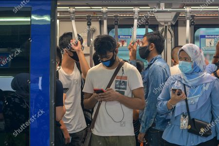 People wearing masks stand in a metro train in Kuala Lumpur, Malaysia, Oct. 5, 2020. Malaysian Prime Minister Muhyiddin Yassin said Monday that he will self quarantine for 14 days after a cabinet minister attending a recent meeting he chaired tested positive of COVID-19.     The announcement came when Malaysia reported another daily record high of 432 new COVID-19 infections on Monday, bringing the national total to 12,813.
