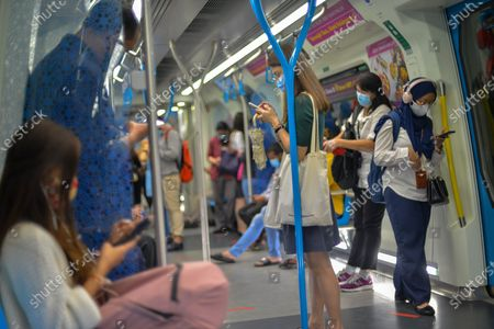 People wearing masks ride a metro train in Kuala Lumpur, Malaysia, Oct. 5, 2020. Malaysian Prime Minister Muhyiddin Yassin said Monday that he will self quarantine for 14 days after a cabinet minister attending a recent meeting he chaired tested positive of COVID-19.     The announcement came when Malaysia reported another daily record high of 432 new COVID-19 infections on Monday, bringing the national total to 12,813.