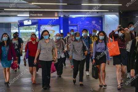 People wearing masks walk in a metro station in Kuala Lumpur, Malaysia, Oct. 5, 2020. Malaysian Prime Minister Muhyiddin Yassin said Monday that he will self quarantine for 14 days after a cabinet minister attending a recent meeting he chaired tested positive of COVID-19.     The announcement came when Malaysia reported another daily record high of 432 new COVID-19 infections on Monday, bringing the national total to 12,813.
