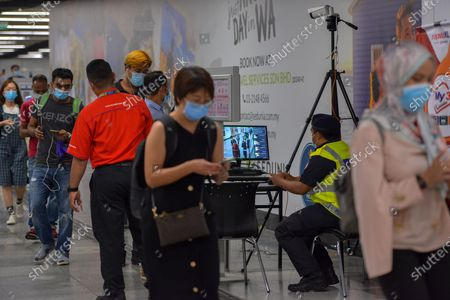 People wearing masks have their body temperature checked in a metro station in Kuala Lumpur, Malaysia, Oct. 5, 2020. Malaysian Prime Minister Muhyiddin Yassin said Monday that he will self quarantine for 14 days after a cabinet minister attending a recent meeting he chaired tested positive of COVID-19.     The announcement came when Malaysia reported another daily record high of 432 new COVID-19 infections on Monday, bringing the national total to 12,813.