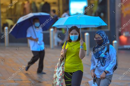 People wearing masks walk on a street in Kuala Lumpur, Malaysia, Oct. 5, 2020. Malaysian Prime Minister Muhyiddin Yassin said Monday that he will self quarantine for 14 days after a cabinet minister attending a recent meeting he chaired tested positive of COVID-19.     The announcement came when Malaysia reported another daily record high of 432 new COVID-19 infections on Monday, bringing the national total to 12,813.