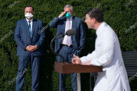 White House director of social media Dan Scavino, left, and White House chief of staff Mark Meadows, center, listen as Dr. Sean Conley, physician to President Donald Trump, talks with reporters at Walter Reed National Military Medical Center, in Bethesda, Md