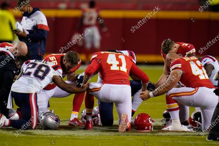 Stock Picture of New England Patriots running back James White (28), Kansas City Chiefs linebacker Ben Niemann (56), James Winchester (41) and Kansas City Chiefs running back Anthony Sherman (42) hold hands to pray after an NFL football game, in Kansas City. The Chiefs won 26-10