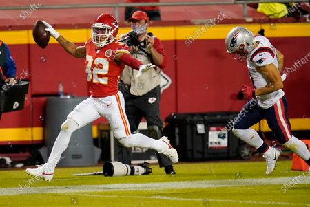 Kansas City Chiefs safety Tyrann Mathieu (32) runs from New England Patriots wide receiver Julian Edelman, right, while returning an interception 25-yards for a touchdown during the second half of an NFL football game, in Kansas City