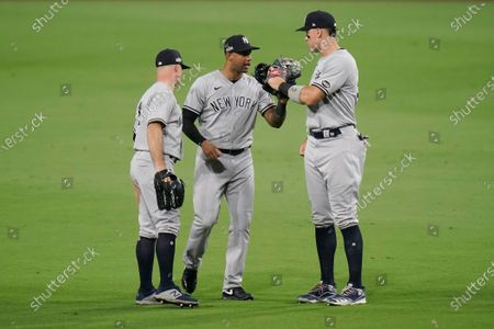 From left, New York Yankees left fielder Brett Gardner, center fielder Aaron Hicks and right fielder Aaron Judge celebrate after the Yankees beat the Tampa Bay Rays 9-3 in Game one of a baseball American League Division Series, in San Diego