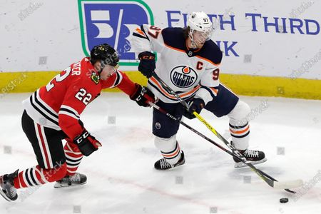 Edmonton Oilers center Connor McDavid, right, and Chicago Blackhawks center Ryan Carpenter vie for the puck during the first period of an NHL hockey game in Chicago. The Oilers say McDavid has tested positive for COVID-19. The team says the star forward is self-quarantining at home and experiencing mild symptoms