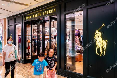 Pedestrians walk past a Polo Ralph Lauren store.