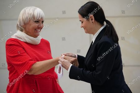 Belarusian opposition leader Svetlana Tikhanovskaya (R) gives a white red ribbon to the Vice President of the German Parliament Claudia Roth as she attends a Green Party (Buendnis 90/Die Gruenen) faction meeting at the Reichstag building, the seat of the German Parliament, in Berlin, Germany, 06 October 2020. Belarusian opposition leader Svetlana Tikhanovskaya is on a visit to Berlin at the moment.