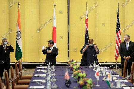 Subrahmanyam Jaishankar, India's foreign minister, from left, Toshimitsu Motegi, Japan's foreign minister, Marise Payne, Australia's foreign minister, and Michael Pompeo, U.S. Secretary of State, remove their protective face masks before posing for a photograph prior to the Quadrilateral Security Dialogue (Quad) ministerial meeting in Tokyo, Japan, 06 October 2020.