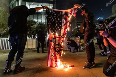 People set an American Flag on fire in protest of the murder of Jonathan Price by Texas police officer Shaun David Lucas