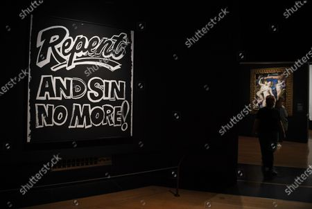 A gallery employee walks an artwork titled 'Repent and sin no more!' by Andy Warhol during a photocall of the exhibition 'Sin' in the National Galley in London, Britain, 06 October 2020. The exhibition will open to the public on 07 October and runs until 03 January 2021.