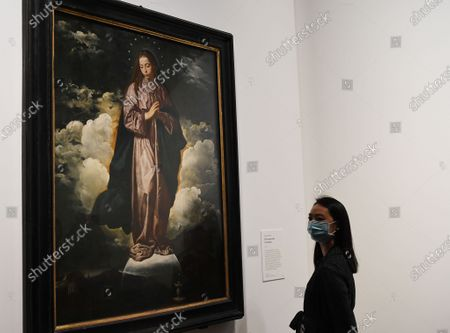 Stock Image of A gallery employee poses next to the artwork 'The Immaculate Conception' by Diego Velazquez during a photocall of the exhibition 'Sin' in the National Galley in London, Britain, 06 October 2020. The exhibition will open to the public on 07 October and runs until 03 January 2021.