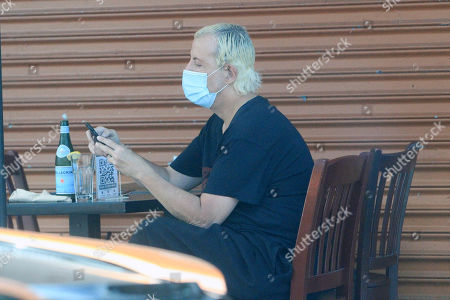 Stock Picture of Steven Cojocaru sits down at a restaurant