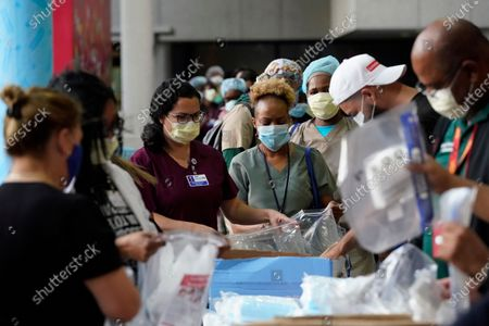 Stock Photo of Healthcare workers line up for free personal protective equipment in front of murals by artist Romero Britto at Jackson Memorial Hospital, in Miami. Hundreds of workers lined up for the PPE provided by the New York nonprofit Cut Red Tape 4 Heroes