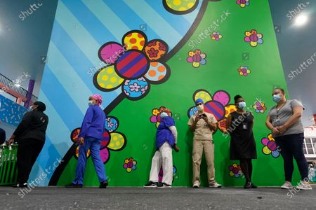 Stock Picture of Healthcare workers line up for free personal protective equipment in front of murals by artist Romero Britto at Jackson Memorial Hospital, in Miami. Hundreds of workers lined up for the PPE provided by the New York nonprofit Cut Red Tape 4 Heroes