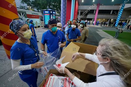 Healthcare workers line up for free personal protective equipment in front of murals by artist Romero Britto at Jackson Memorial Hospital, in Miami. Hundreds of workers lined up for the PPE provided by the New York nonprofit Cut Red Tape 4 Heroes