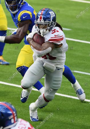 New York Giants running back Devonta Freeman (31) gains yards on a run during an NFL football game against the Los Angeles Rams, in Inglewood, Calif. The Rams defeated the Giants 17 -9