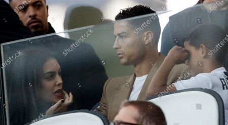 Juventus forward Cristiano Ronaldo, center, is flanked by his girlfriend Georgina, left, and his son Cristiano Jr, as he sits in the stands during a Champions League, group H soccer match between Juventus and Young Boys, at the Allianz stadium in Turin, Italy. Ronaldo's legal fight with a woman who accuses the international soccer star of raping her in his suite at a Las Vegas resort more than 10 years ago is heading toward a court hearing before a federal judge in Las Vegas