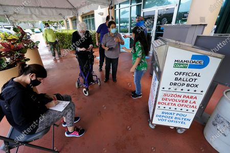 Voters prepare to turn in their mail-in ballots, at the Miami-Dade County Elections Department in Doral, Fla. Florida Gov. Ron DeSantis extended the state's voter registration deadline after heavy traffic crashed the state's online system and potentially prevented thousands of enrolling to cast ballots in next month's presidential election