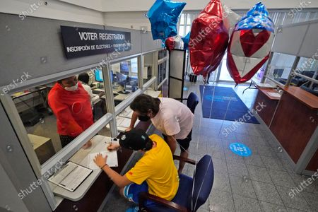 Lucas Saez, foreground, 22, fills out his voter registration form as his father Ramiro Saez, center rear, looks, at the Miami-Dade County Elections Department in Doral, Fla. Florida Gov. Ron DeSantis extended the state's voter registration deadline after heavy traffic crashed the state's online system and potentially prevented thousands of enrolling to cast ballots in next month's presidential election. Saez attempted to register to vote six times the night before without any luck
