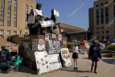 People walk past a statue of Abraham Lincoln covered with pictures and names of Black people who have died in confrontations with police and demands that police Chief Rick Smith be fired in front of City Hall, in Kansas City, Mo. Activists, outraged after a white Kansas City police officer knelt on the back of a pregnant Black woman during an arrest last week are camping outside city hall and plan to stay until the officer and the police chief are fired
