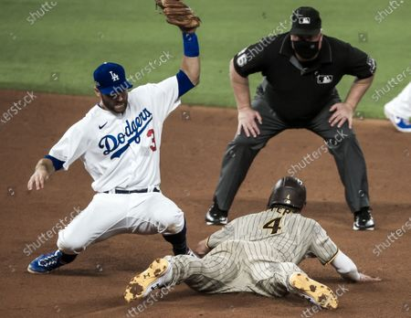 Second base umpire Bill Miller (R, top) watches as San Diego Padres right fielder Wil Myers (R, bottom) steals second base on Los Angeles Dodgers second baseman Chris Taylor (L) in the fourth inning of the MLB National League Division Series baseball game between the San Diego Padres and the Los Angels Dodgers at Globe Life Field in Arlington, Texas, USA, 06 October 2020.