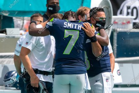 From left, Seahawks quarterback coach Austin Davis, Seattle Seahawks quarterback Geno Smith (7) and Seattle Seahawks quarterback Russell Wilson (3) embrace in a circle as they stand on the sidelines during the singing of The National Anthem before taking on the Miami Dolphins during an NFL football game, in Miami Gardens, Fla