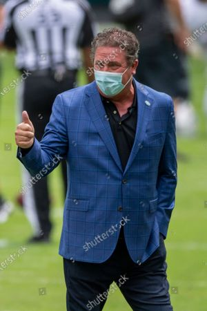 Dan Marino wears a mask and gives a thumbs up on the field before the Seattle Seahawks take on the Miami Dolphins during an NFL football game, in Miami Gardens, Fla