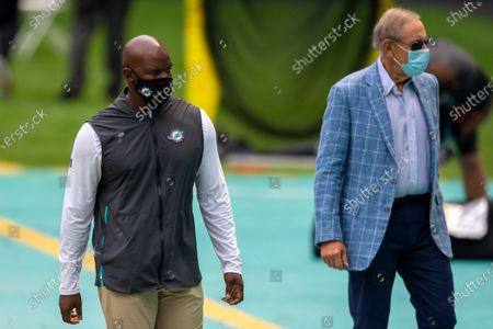 Miami Dolphins head coach Brian Flores and Miami Dolphins owner Stephen Ross wearing masks on the sidelines before taking on the Seattle Seahawks during an NFL football game, in Miami Gardens, Fla