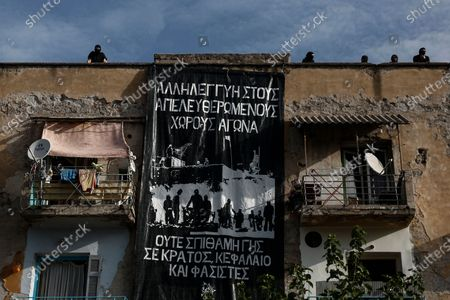 Anarchist protesters hang a banner on a building next to the Athens' courthouse, as they wait for the verdict of the trial for the ultra-right party Golden Dawn's (Chrysi Avgi) in Athens, Greece, 07 October 2020. The verdict in the trial of the ultra-right party Golden Dawn - a trial unprecedented on a global scale in recent history - is due to be announced by an Athens Criminal Appeals Court. With its ruling, the court is called on to decide whether the accused are guilty or not guilty of forming a criminal organisation and to provide an answer to an issue of critical legal and social importance, which will have a profound impact on the present and future, regarding a political party that was elected to the Greek and European parliaments in three separate elections. Based on the charges, Golden Dawn was a criminal organisation that had the legal form of a party and enjoyed enhanced constitutional protection as a result.