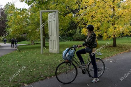 """Stock Image of A woman views """"L'Age D'Or (Green & Red)"""", 2019, by Gavin Turk at Frieze Sculpture, an annual exhibition of outdoor works by international artists in Regent's Park. The works are on display to the public until 18 October."""